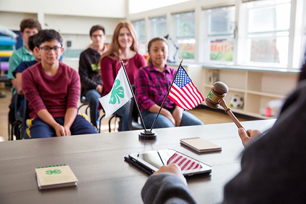 The setting for a 4-H meeting showing someone using a gavel, the 4-H and American flags, and several youth sitting in chairs