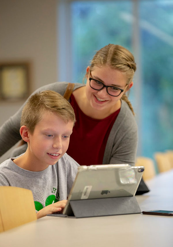 Female teen assisting a young boy on an iPad