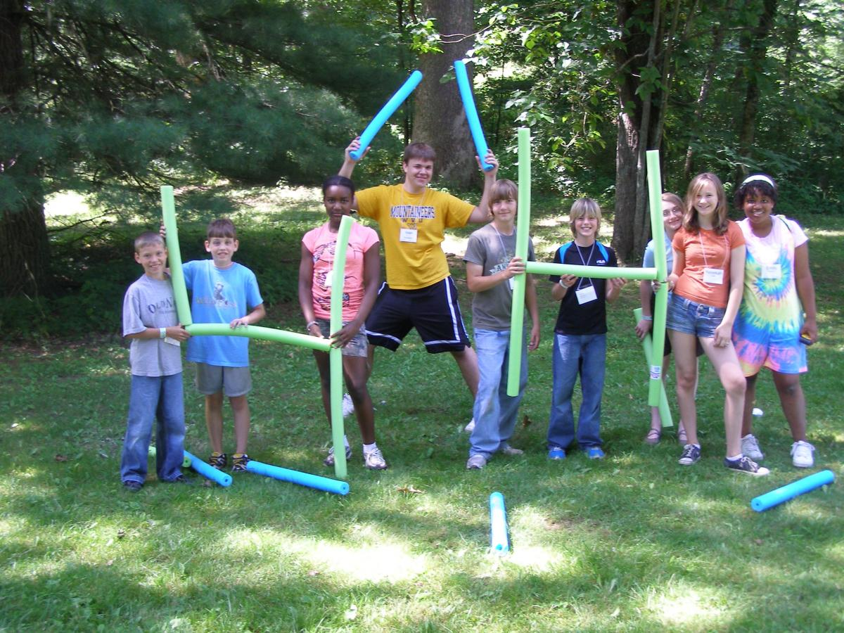 Nine kids using styrofoam pool noodles to spell out 4-H