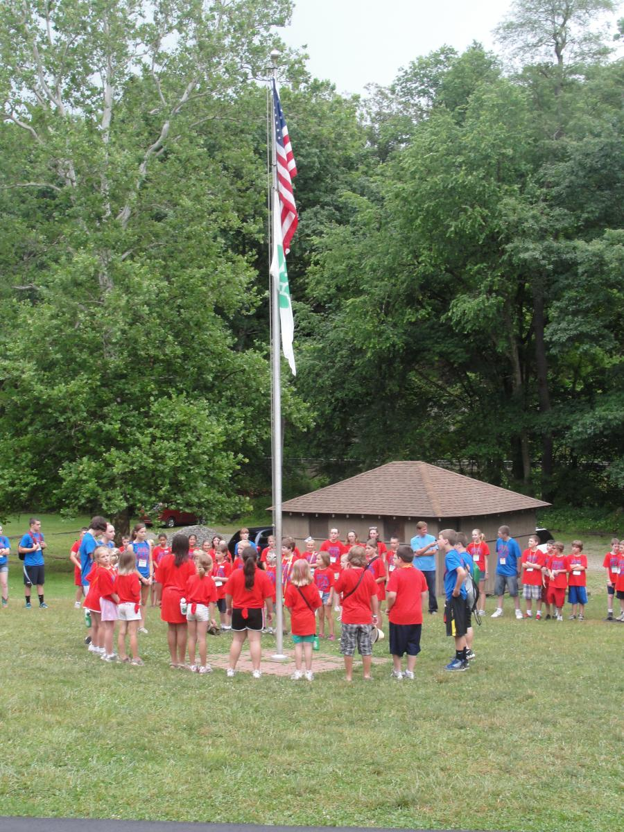 Image of kids in red shirts around a flagpole, holding hands at camp for flag raising activity