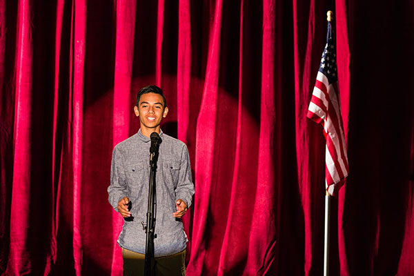 Teen boy standing at a microphone speaking. United States flag on the right side of the photo.