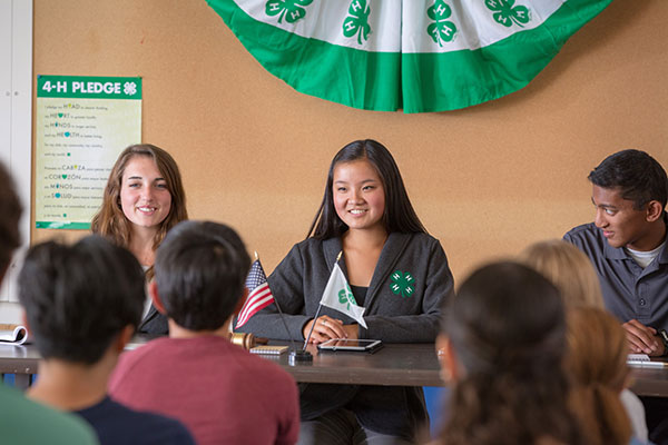 Three 4-H teen leaders sitting at a head table in front of a group of youth.