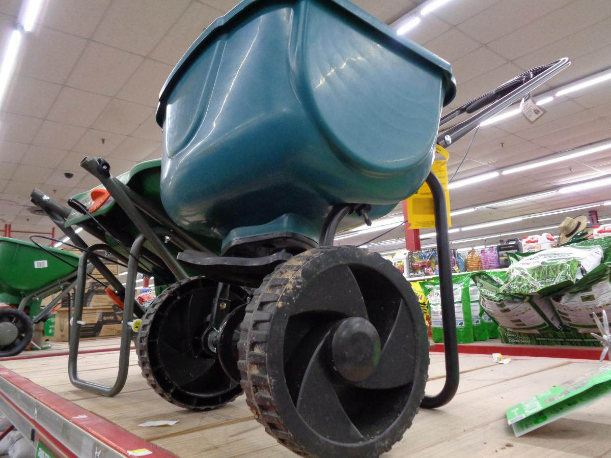 Manual fertilizer spreader with a black frame and teal blue hopper on sturdy wheels.