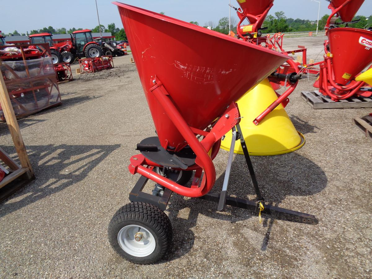 Red fertilizer spreader with black wheels