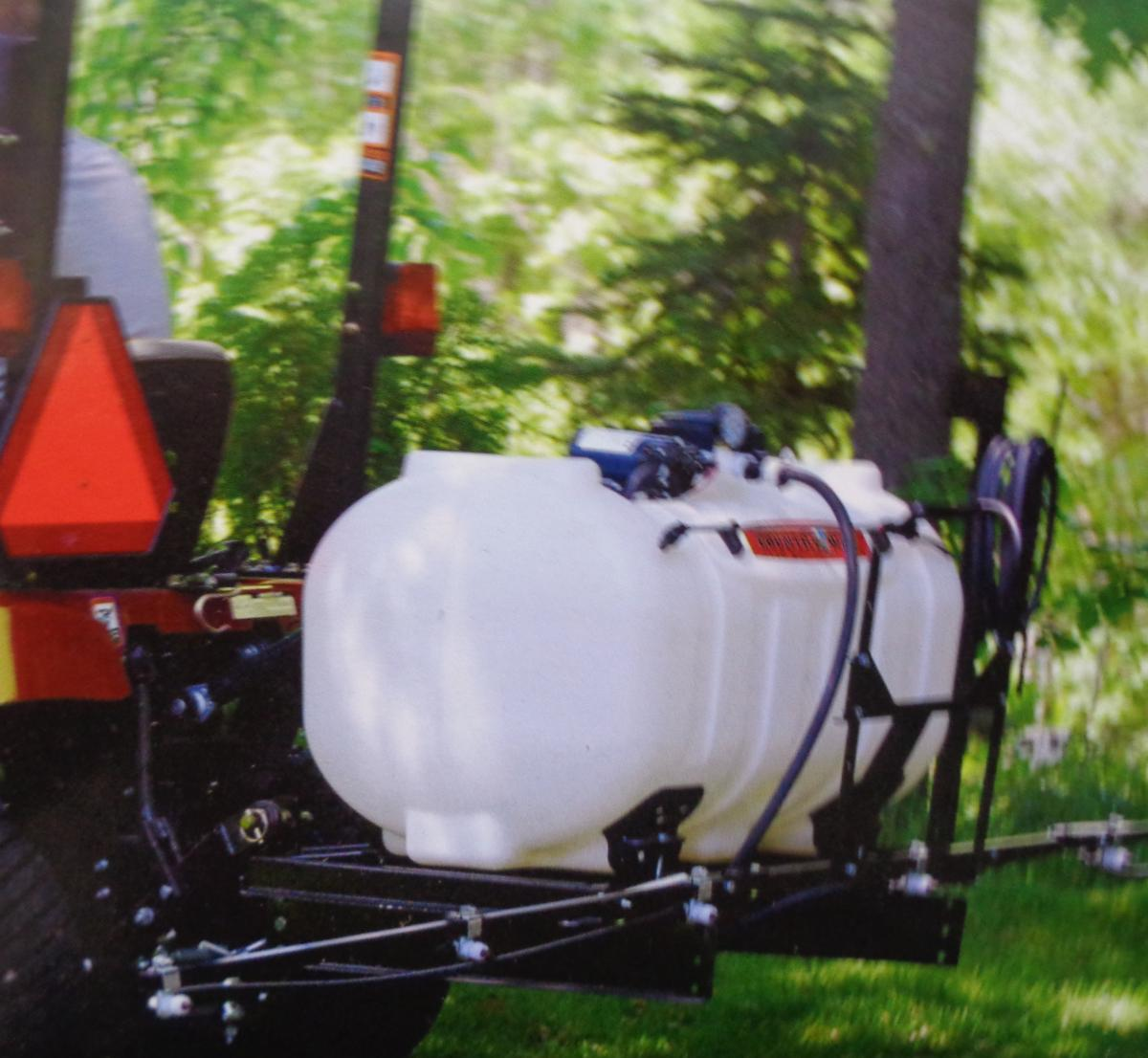 Large white plastic sprayer on an ATV with neon orange safety triangle.