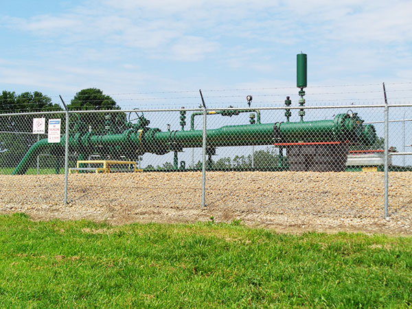 Photo of fenced area containing large above ground pipes, valve assemblage, and pig launching site.