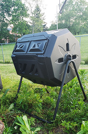 A black plastic bin is on tubular steel legs in a grassy field with trees in the background.