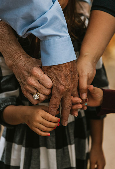 Grandfather's hand being held by grandmother, mother, and grandchildren.