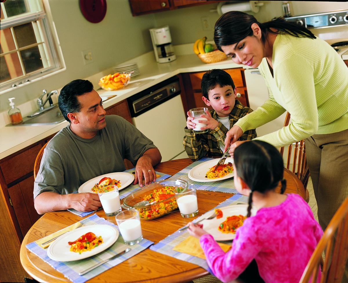 Photo of a Latino family sharing a meal together in their kitchen.
