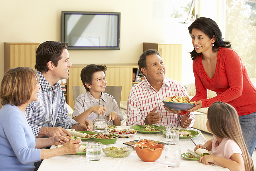 Image of family being served dinner, around table.
