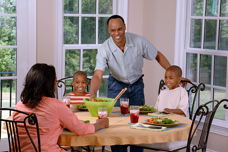 A family around a table with a meal on the table, salad and drinks.