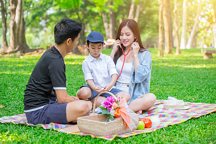 A family of three enjoys a picnic in a park.