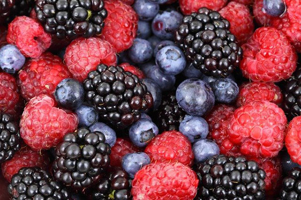 A close up of a mix of blackberries, red raspberries, and blueberries.
