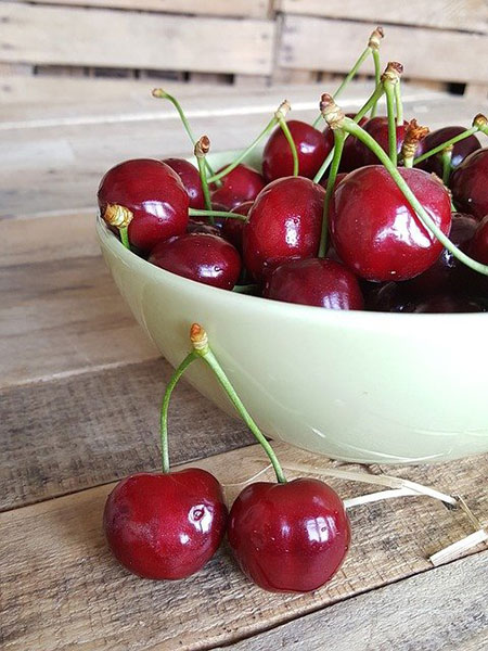 Close up of dark red cherries in a light green bowl with two cherries displayed prominently on the tabletop outside the bowl.
