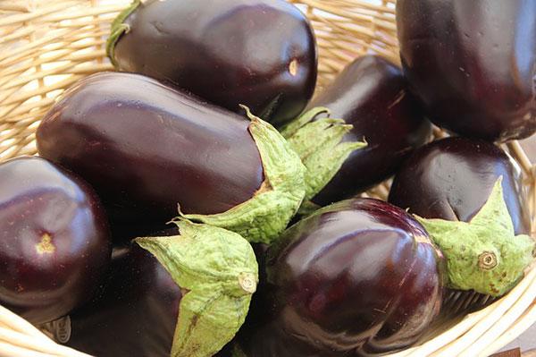 Dark purple eggplants in a wicker basket.