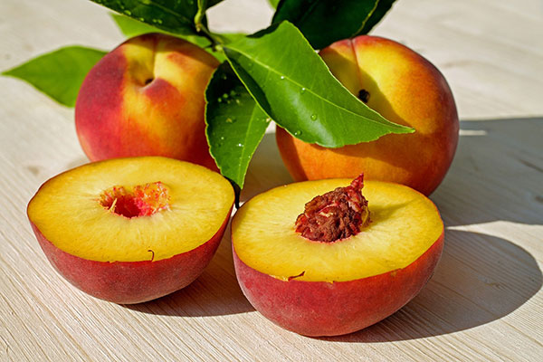 Two halves of a cut peach in front of two whole peaches and a few peach tree leaves.