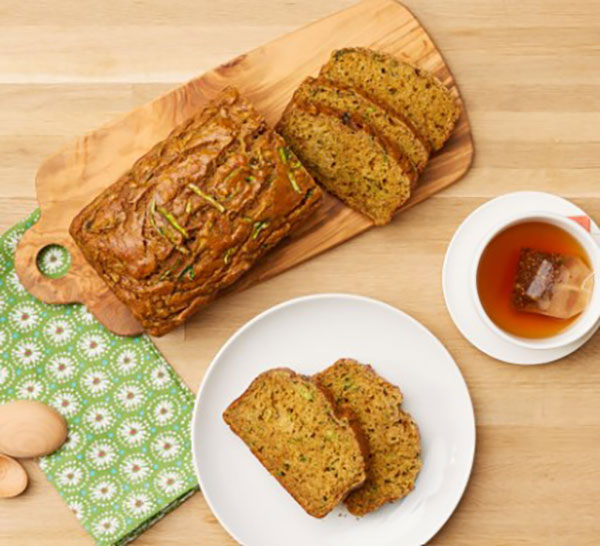 Loaf of zucchini pumpkin bread on cutting board with two slices on plate next to a cup of tea.