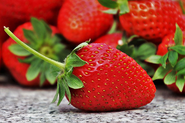 Close up of strawberry with strawberries out of focus in the background.