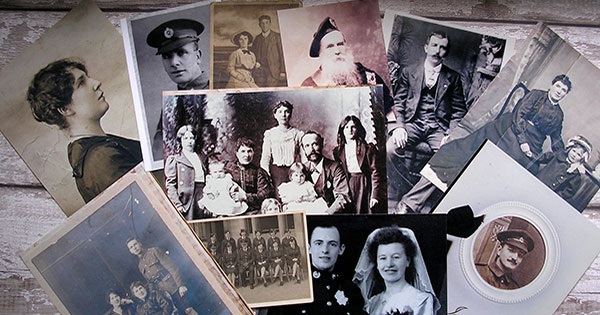 Black and white and sepia-colored genealogical photos spread on tabletop.