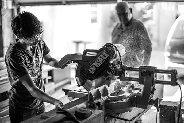 Grandfather oversees grandson cutting wood with a power saw.