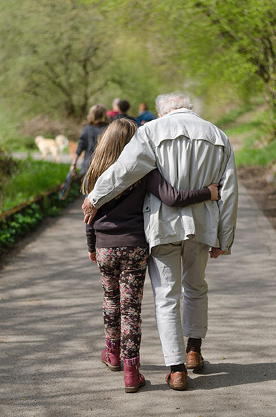 Grandfather and granddaughter walking together through a park.