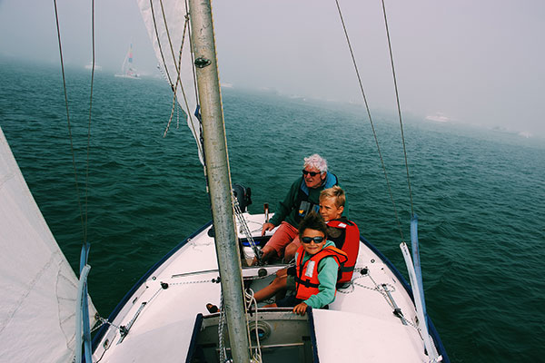 Grandfather sailing with his two grandsons.