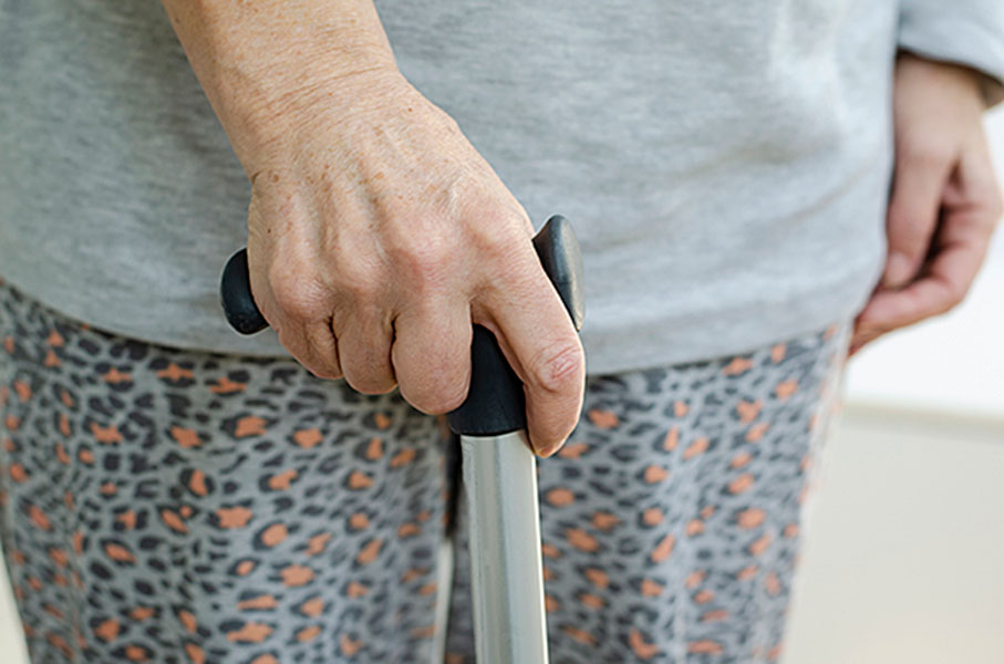 An elderly woman standing while holding a metal cane in her hand
