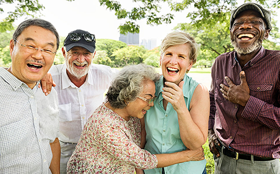 A friendly, happy, laughing group of three older men and two older women stand close together, some with their arms on another's shoulders or around another's waist.