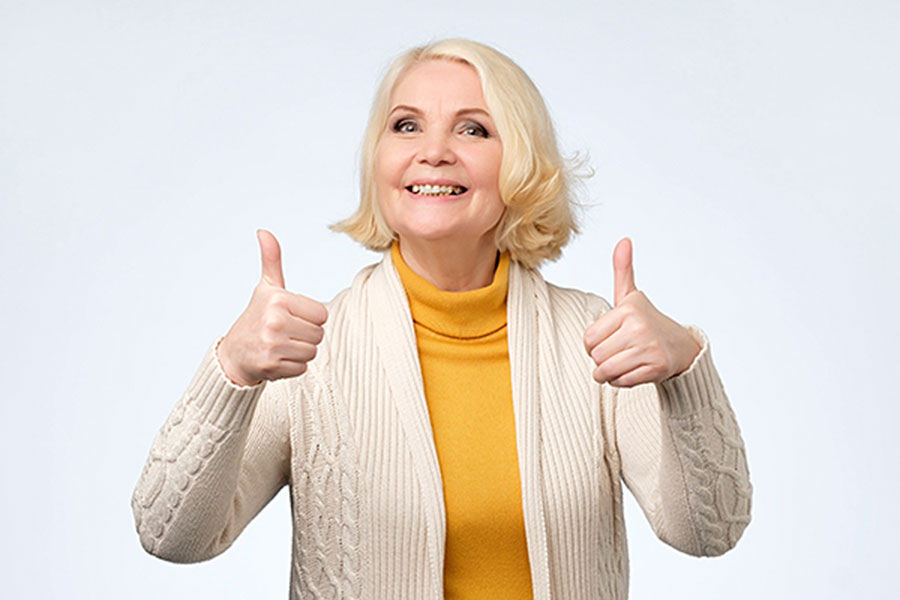 """An older female is smiling broadly as she gives the """"thumbs up"""" signal by holding her hands in fists and raising her thumbs."""
