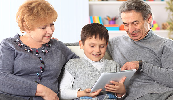 Smiling grandparents and their grandson sit together on a couch, as the grandfather points out something on a computer tablet held by the child.