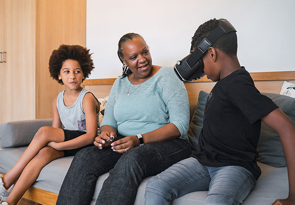 A smiling grandmother, granddaughter, and grandson sit on a couch, as the boy demonstrates 3-D glasses for the group.