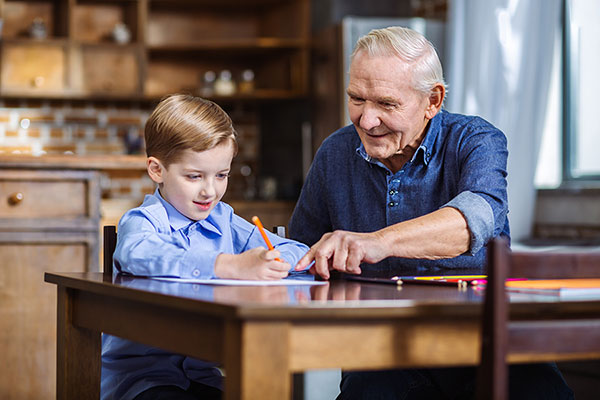 : A happy grandfather sits at a table with his smiling grandson, helping the boy with writing.