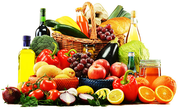 Loose fruits, vegetables, and bottles of oils together with baskets holding more of the same items.