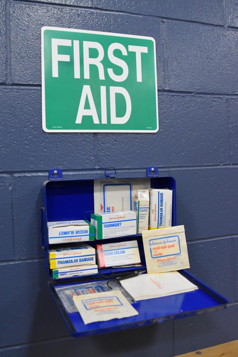 Photo of a first-aid kit open with bandages, tape, gauze in a blue box.