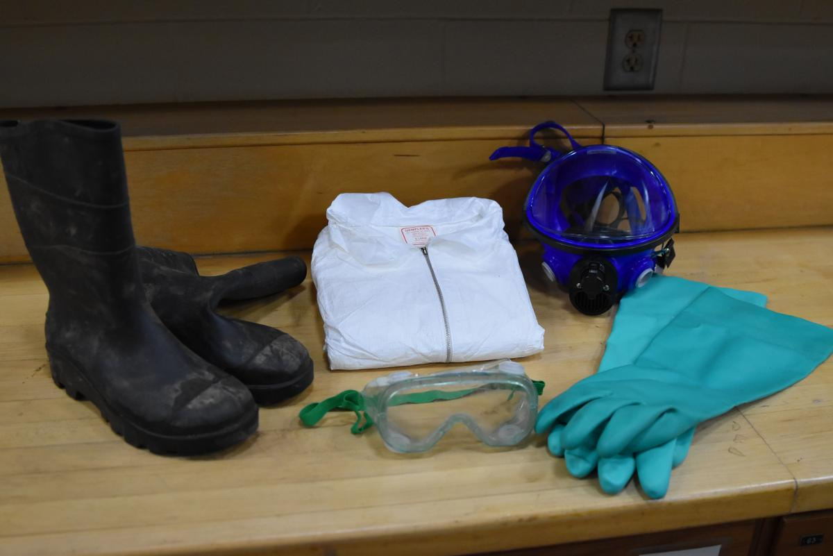 Array of pesticide protective clothing, including rubber boots, gloves, shirt, face mask and goggles.