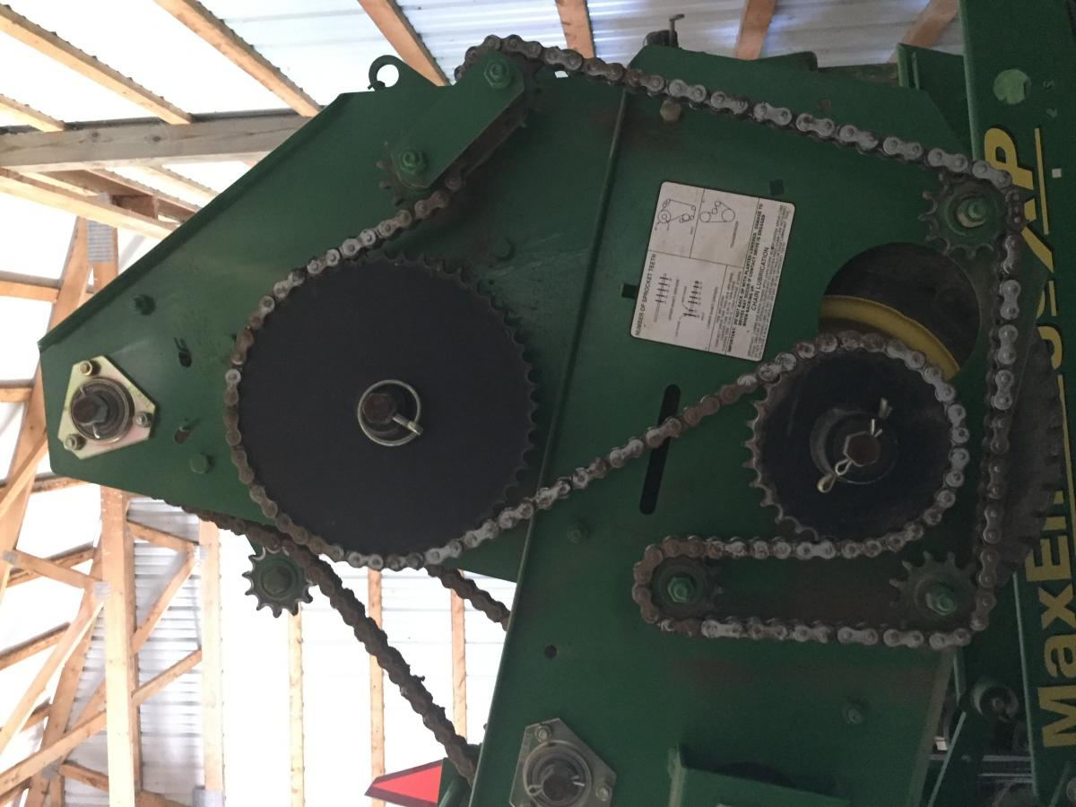 Green farm equipment with chain on rollers