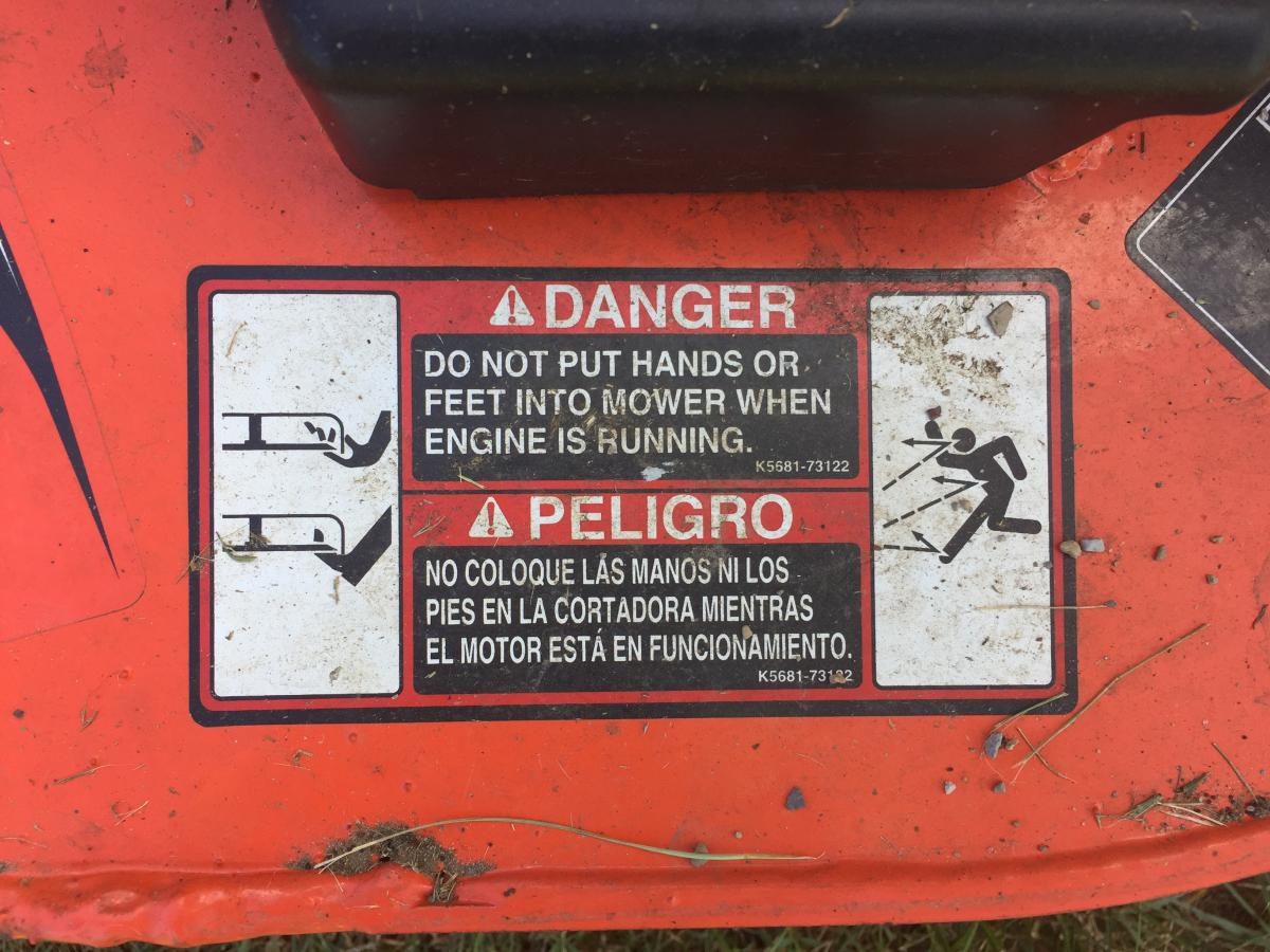 Closeup of Danger sign in English and Spanish, warning user to not put hands or feet into mower when engine is running