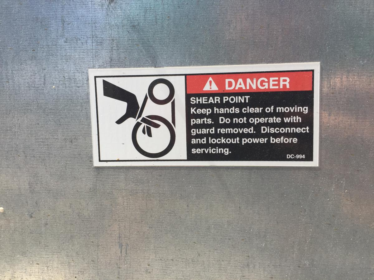 Closeup of a Danger sign on a piece of machinery, fingers getting pulled into a shear point on a chain