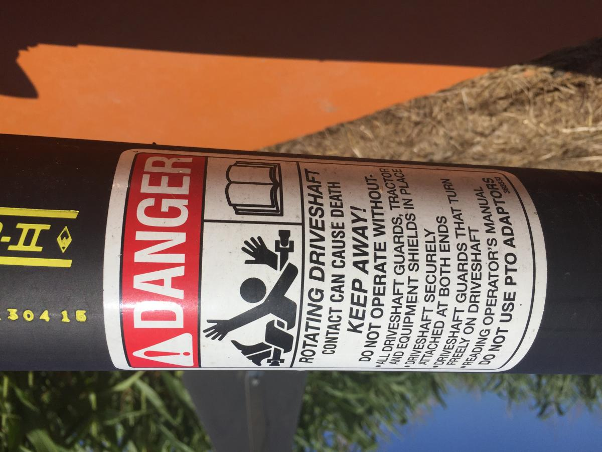 Closeup of drive shaft danger sign, warning that contact can cause death. Drive shafts need guards when operating