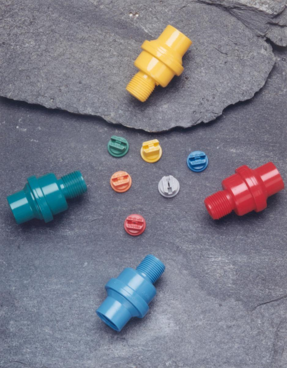 Four nozzles in yellow, red, green and blue on slate background