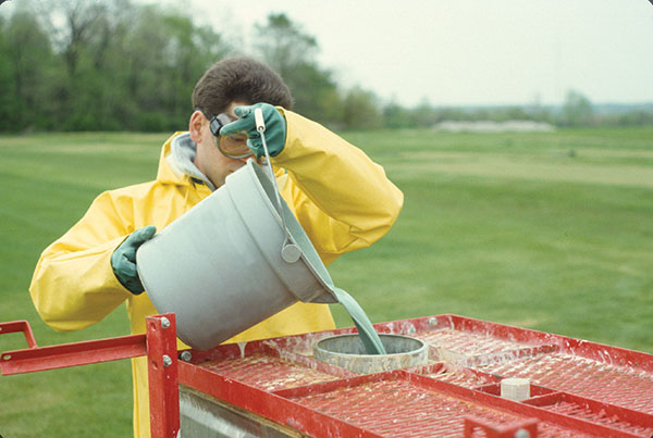 Man in safety goggles, gloves and clothing pouring spray into machine.