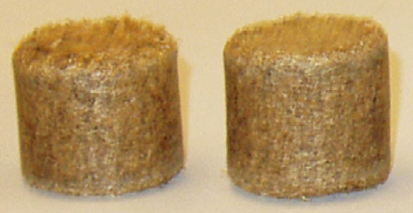 Two rounded briquettes with a flat top and bottom, created by compressing ground wood.